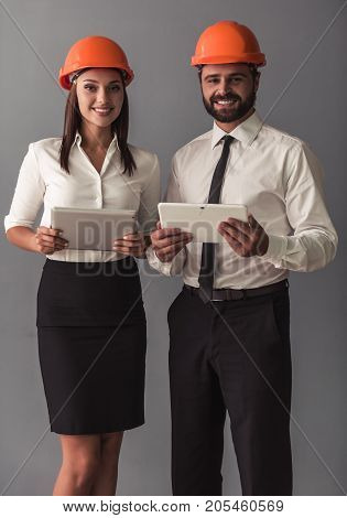 Handsome businessman and beautiful business woman in suits and protective helmets are using digital tablets looking at camera and smiling on gray background