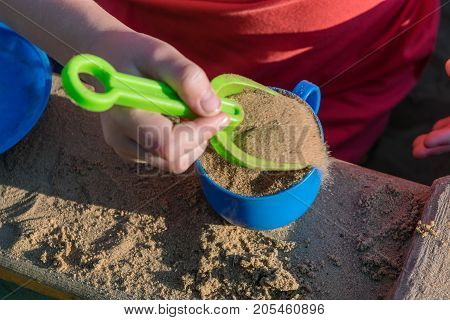 A small child puts a toy in a blue mug green sand shovel. Scoop and a plastic mug. Girl holding a scoop hand. Play in the sandbox.