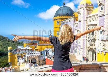 Carefree caucasian woman with open arms at Pena National Palace. Palacio da Pena is a Unesco Heritage and one of Seven Wonders of Portugal. Female tourist enjoys of most visited attraction of Sintra.