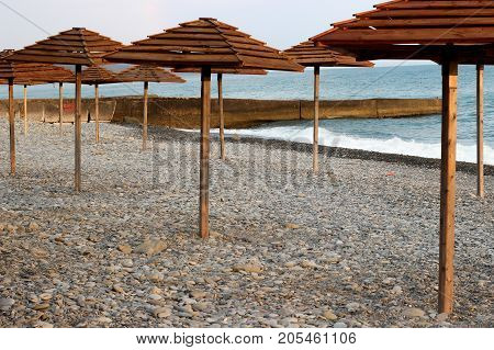 wooden umbrellas on the beach, umbrellas on the coast, beach and awnings
