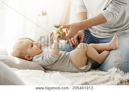 Little baby boy spending happy childhood with young mother. Child trying to take a beautiful toy from tender mom hands. Family concept