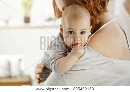 Portrait of sweet little child looking at camera with big grey eyes and putting hand in mouth on mother shoulder. Mom hug her child with love. Family concept