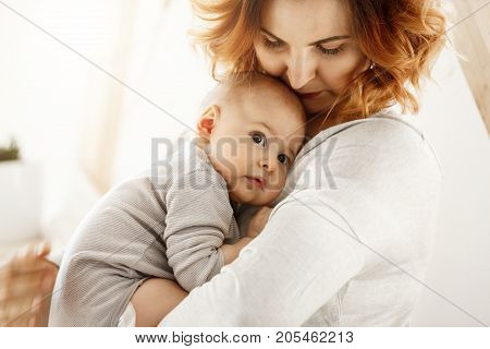 Beautiful young mother tenderly hugs her little cute child. Mom looking at her kid and smiling while baby looks aside and snuggling to mom chest. Happy family moments