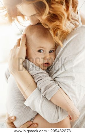Portrait of sweet little child looking in the camera with interested expression while mother tenderly snuggle palming and kissing her newborn baby