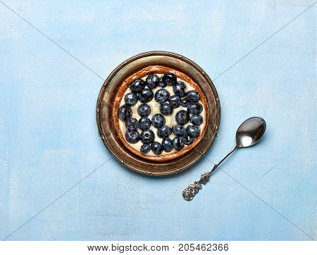 Blueberry tart, pie, tartlet with custard on blue stone background.