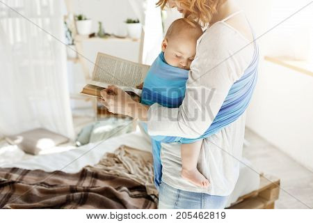Tiny sweet babyboy peacefully sleeping on mother in baby sling while young beautiful mom trying to relax reading favorite book