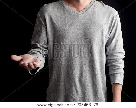 Young man giving empty hand on black background.Hands open businessman. some object are here.