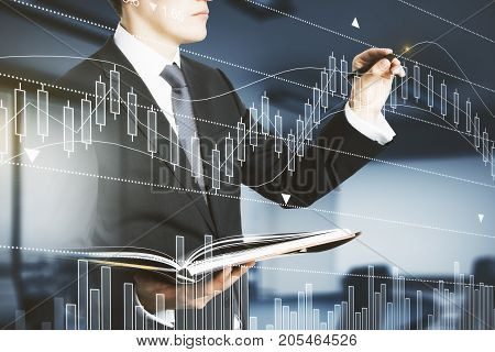 Side view of handsome businessman with document in hands drawing abstract forex chart in blurry interior with sunlight. Broker concept. Double exposure