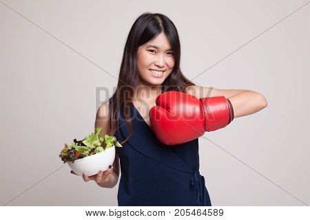 Young Asian Woman With Boxing Glove And Salad.