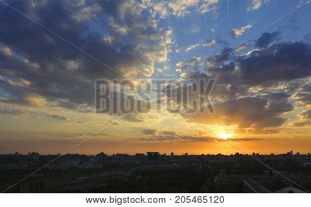 The silhouette of a sleeping city against the background of a fiery reddish sunrise the rays of which are dispersed by the clouds