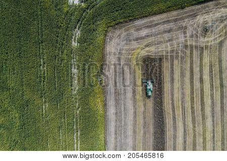 Harvester machine working in field . Combine harvester agriculture machine harvesting golden ripe wheat field. Agriculture. Aerial view. From above. Corn field. Top view, from above. Geometric pattern from the landscape
