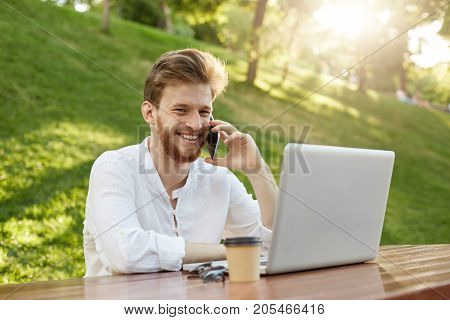 Young handsome european financial manager with stylish hair and beard, looks at laptop monitor and talking happily with boss about profit from last month in his company