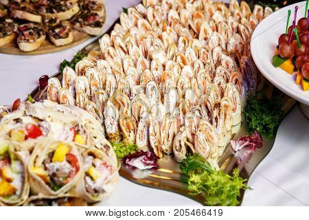 Rolls of thin pancakes with smoked salmon, horseradish cream cheese and rocket leaves on event catering