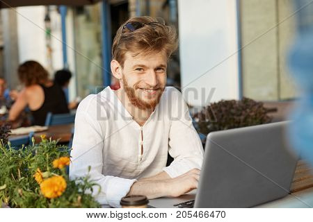 Young good looking european with ginger hair and beard, smiles, looking at camera with happy and excited expression, posing for article about startupers