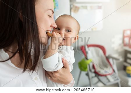 Close up of cute newborn baby boy feeding happy mother with cookie, smiling and looking aside. Lifestyle, family, motherhood concept
