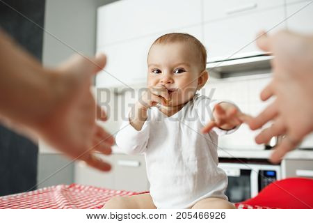 Portrait of joyful little boy sitting in kitchen, holding hand in mouth and pulling hands to mother. Mom hands on foreground.