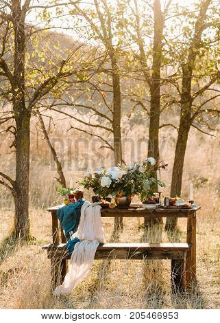 surprise, engagement, design concept. private and romantic place among the fields and groves, there is wonderful wedding bouquet in bronze vase, candles, fruits and glowing glasses of wine
