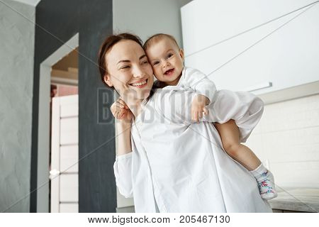 Handsome young mother playing with little baby boy holding him on back with hands. Child brightfully smiling and feeling happy