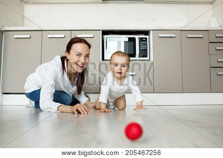 Joyful beautiful mother and little baby son with big brown eyes playing together with red ball in kitchen. Scene of family happiness