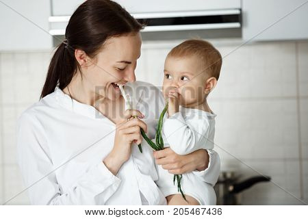 Funny portrait of young beautiful mother looking at her little boy while he looking at her with curious expression. They eating green onion at kitchen