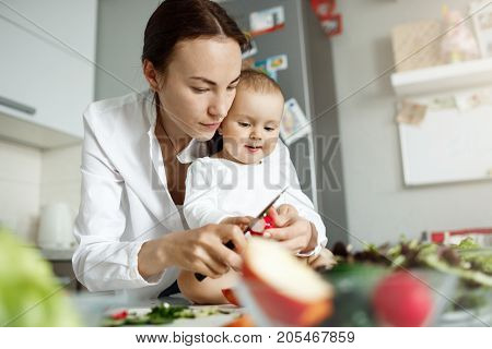 Serious young good-looking mother spending time with her newborn son cooking dinner and showing how to cut vegetables