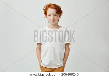 Cute redhead boy with good-looking hairstyle in white t-shirt holding holding hands in pockets, gently smiling and looking in camera