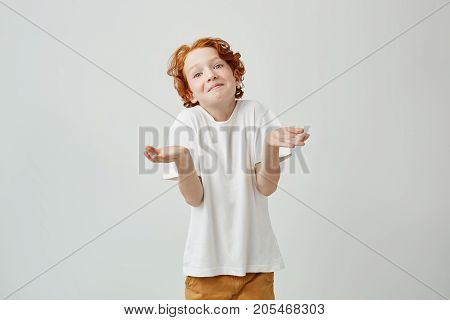 Portrait of lovely little kid with bright red hair gesticulating with hands showing the don't know answer on teacher question