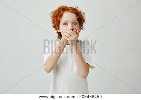 Little cute ginger boy with green eyes in white t-shirt clothing mouth with hands, being scared watching horror film with friends