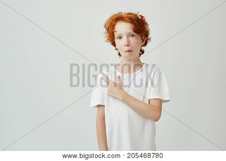 Funny ginger boy with freckles having curious expression and pointing a side with finger on white wall. Copy space for advertisement