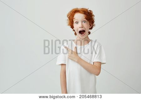 Portrait of joyful ginger child with freckles posing with opened mouth and crazy expression, pointing at free space for advertisement. Copy space