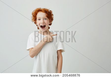 Cheerful cute little boy with curly ginger hair and freckles happy smiling and pointing aside with finger on white background. Copy space