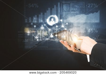 Side view and close up of businessman hands using tablet with digital business hologram on dark background. Device and media concept. Double exposure