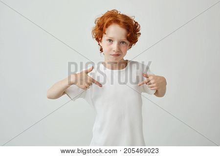 Close up of red haired cute boy with freckles pointing with fingers on white t shirt with serious and confident expression. Copy space