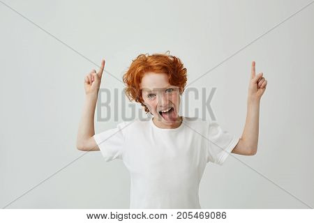 Close up of funny little boy with curly ginger hair and freckles pointing up with both hands, having silly face with open mouth. Copy space