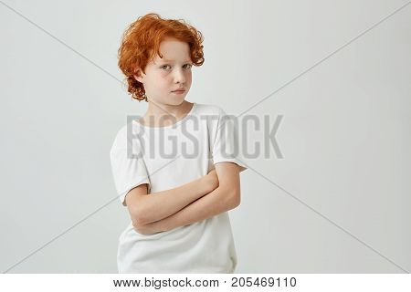 Close up portrait of funny ginger boy with freckles in white t-shirt looking in camera with relaxed expression and crossed hands