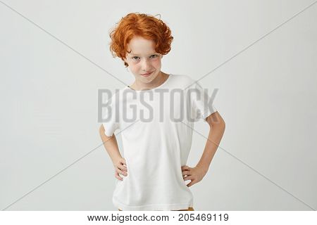 Isolated portrait of funny ginger boy in white t-shirt holding hands on waist, looking in camera with confident expression. Copy space