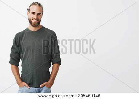 Handsome nordic man with beard and stylish hairstyle in grey shirt and jeans smiling, looking in camera, holding hands in pockets.