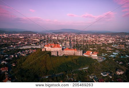 Beautiful panoramic view from the air to Palanok Castle at sunset and the city of Mukacheve