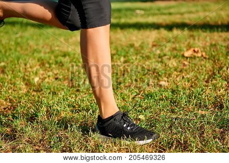 Close up of the legs of a young woman who is running off road in a park