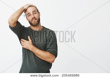 Good-looking man with stylish hairstyle and beard with happy expression finally can breathe easier after finding phone under table in cafeteria