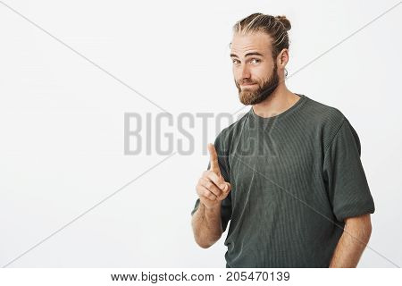 Portrait of good-looking nordic man showing index finger asking to wait for a minute while he clean hands in toilet. Body language