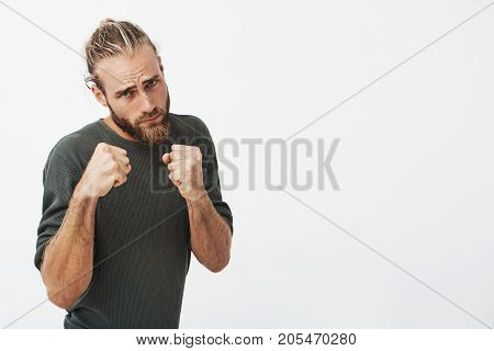 Strong attractive guy with stylish hairstyle and beard holding hands in front of chest going to punch in face man who offended his girlfriend