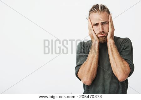 Portrait of beautiful bearded man holding head in hands with unhappy expression watching sad movie about animals and trying not to cry