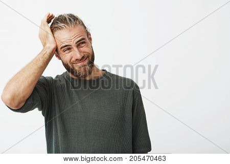 Portrait of attractive bearded man holding hand on forehead with guilty expression after remembering he forgot to phone mother on her birthday.