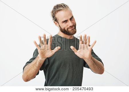 Portrait of beautiful young guy with trendy haircut and beard gesticulating with both hands, showing ten fingers with funny face expression