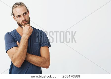 Close up portrait of beautiful bearded man with stylish hairstyle and clothes looking aside and thinking about rooms design