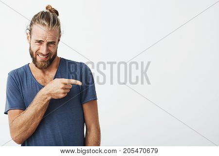 Close up portrait of attractive bearded man with trendy hairstyle pointing at white wall with disgust expression. Copy space