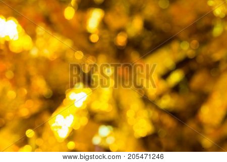 Christmas background with shimmering glitter. Defocused lights. Gold and yellow Christmas tinsel is as Christmas light Abstract background