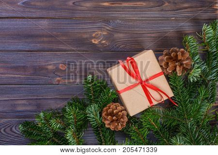 Christmas composition. Christmas gift knitted blanket pine cones fir branches on wooden white background. Flat lay top view.