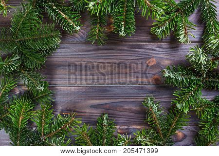 Round frame made of Christmas pine tree branches on old wooden board. Space for text. Top view.